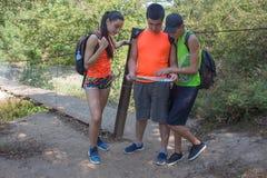 Ταξιδιώτες, οδοιπόροι στις διακοπές που διαβάζουν έναν χάρτη Οι ταξιδιώτες ταξιδεύουν στην επιφύλαξη υγιής τρόπος ζωής στις θεριν Στοκ Φωτογραφίες