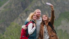 Ταξιδιώτες φίλων με backpacks do selfie στο τηλέφωνο στα βουνά Μια ομάδα τουριστών παίρνει τις εικόνες στο τηλέφωνο φιλμ μικρού μήκους