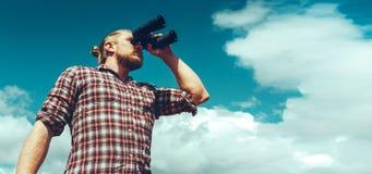 Ταξιδιώτης ατόμων έννοιας αναζήτησης περιπέτειας που κοιτάζει μέσω των διοπτρών στην απόσταση ενάντια στον ουρανό Χαμηλός βλαστός Στοκ Φωτογραφία