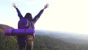 Ταξιδιώτης γυναικών με το σακίδιο πλάτης με τα αυξημένα χέρια πάνω από το βουνό, οπισθοσκόπο απόθεμα βίντεο