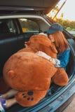 Ταξιδιώτης γυναικών που ξαπλώνει στο αυτοκίνητο hatchback και που αγκαλιάζει μια μεγάλη αρκούδα στοκ φωτογραφίες με δικαίωμα ελεύθερης χρήσης
