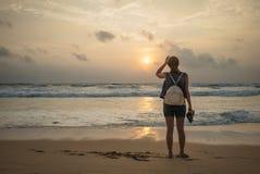 Ταξιδιώτης γυναικών που υπερασπίζεται τη θάλασσα και που εξετάζει το ηλιοβασίλεμα Στοκ φωτογραφία με δικαίωμα ελεύθερης χρήσης