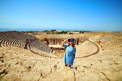 Ταξιδιώτης γυναικών στο καπέλο που εξετάζει τις καταπληκτικές καταστροφές αμφιθεάτρων σε αρχαίο Hierapolis, Pamukkale, Τουρκία Με στοκ εικόνες