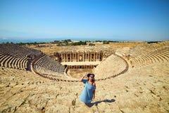 Ταξιδιώτης γυναικών στο καπέλο που εξετάζει τις καταπληκτικές καταστροφές αμφιθεάτρων σε αρχαίο Hierapolis, Pamukkale, Τουρκία Με στοκ εικόνες με δικαίωμα ελεύθερης χρήσης