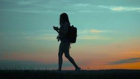 Ταξιδιώτης κοριτσιών οδοιπόρων σκιαγραφιών με τους τρόπους αναζήτησης ναυσιπλοΐας smartphone η ναυσιπλοΐα θέσης αναζήτησης φύσης  φιλμ μικρού μήκους