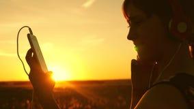 Ταξιδιώτης κοριτσιών που ακούει τη μουσική στο smartphone στις ακτίνες ενός όμορφου ηλιοβασιλέματος άνοιξη νέο κορίτσι με τα ακου απόθεμα βίντεο