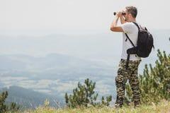 Ταξιδιώτης με το σακίδιο πλάτης που στέκεται στην κορυφή του βουνού και που χρησιμοποιεί τις διόπτρες στοκ εικόνες