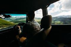 Ταξιδιώτης νεαρών άνδρων που ένα αυτοκίνητο στα βουνά το καλοκαίρι, οπισθοσκόπο από το αυτοκίνητο Στοκ εικόνα με δικαίωμα ελεύθερης χρήσης