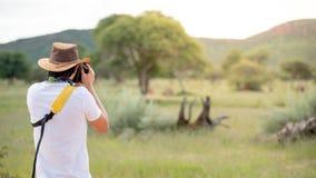 Ταξιδιώτης νεαρών άνδρων που παίρνει τη φωτογραφία των ζώων άγριας φύσης Στοκ Εικόνες