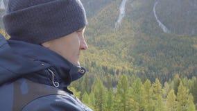 Ταξιδιώτης οδοιπόρων τύπων που στέκεται σε μια μέγιστη σκέψη χαλάρωσης σχεδίου βουνών απόθεμα βίντεο