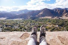 Ταξιδιωτικές ` s μπότες που χαλαρώνουν και που στηρίζονται τα πόδια του στην οδοιπορία υψηλών βουνών και την αρχαίες πόλης σκηνή  στοκ εικόνες