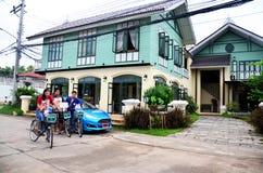 Ταξιδιωτικοί ταϊλανδικοί λαοί που θέτουν με τα ποδήλατα τη στάση στο κλασικό σπίτι Στοκ Φωτογραφία