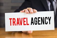 Ταξιδιωτικό γραφείο, μήνυμα στην άσπρη κάρτα και λαβή κοντά στοκ εικόνα με δικαίωμα ελεύθερης χρήσης