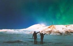 Ταξιδιώτες ζεύγους που απολαμβάνουν τα βόρεια φω'τα Στοκ Φωτογραφίες