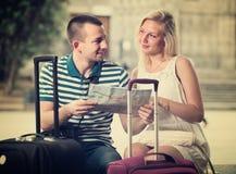 Ταξιδιώτες ζεύγους που κρατούν το χάρτη στοκ φωτογραφίες
