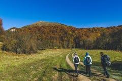 Ταξιδιώτες που περπατούν χρώματα ενός στα contry οδικού φθινοπώρου Στοκ Εικόνες
