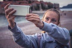 Ταξιδιώτης γυναικών που κάνει selfie την κινητή φωτογραφία στο έξυπνο τηλέφωνο κατά τη διάρκεια των διακοπών ταξιδιού στην παραλί Στοκ Εικόνες