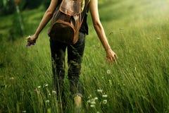 Ταξιδιώτης γυναικών που περπατά μεταξύ της χλόης στο λιβάδι και που κρατά υπό εξέταση Στοκ φωτογραφία με δικαίωμα ελεύθερης χρήσης