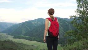 Ταξιδιώτης γυναικών στην άκρη του απότομου βράχου ο τουρίστας κοριτσιών με το σακίδιο πλάτης φιλμ μικρού μήκους