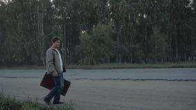 Ταξιδιώτης με μια βαλίτσα που σε μια εθνική οδό απόθεμα βίντεο