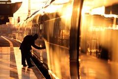 Ταξιδιώτης που ανοίγει μια πόρτα ενός τραίνου κατά τη διάρκεια του ήλιου ρύθμισης Στοκ εικόνες με δικαίωμα ελεύθερης χρήσης