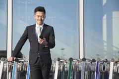 Ταξιδιώτης που εξετάζει το κινητό τηλέφωνο δίπλα στη σειρά των κάρρων αποσκευών Στοκ Φωτογραφία