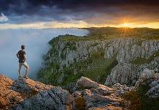 Ταξιδιώτης που στέκεται σε μια άκρη απότομων βράχων Στοκ Φωτογραφίες