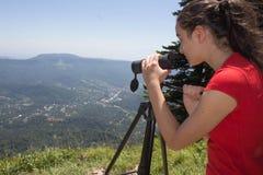 Ταξιδιώτης που φαίνεται η φύση από το υψηλό βουνό με την επισήμανση του πεδίου, τρίποδο διοπτρών στοκ φωτογραφία με δικαίωμα ελεύθερης χρήσης