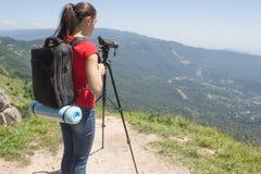 Ταξιδιώτης που φαίνεται η φύση από το υψηλό βουνό με την επισήμανση του πεδίου, τρίποδο διοπτρών στοκ εικόνα