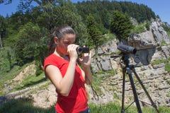 Ταξιδιώτης που φαίνεται η φύση από το υψηλό βουνό με την επισήμανση του πεδίου, τρίποδο διοπτρών στοκ εικόνες