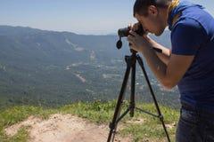 Ταξιδιώτης που φαίνεται η φύση από το υψηλό βουνό με την επισήμανση του πεδίου, τρίποδο διοπτρών στοκ φωτογραφία