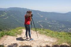 Ταξιδιώτης που φαίνεται η φύση από το υψηλό βουνό με την επισήμανση του πεδίου, τρίποδο διοπτρών στοκ εικόνα με δικαίωμα ελεύθερης χρήσης