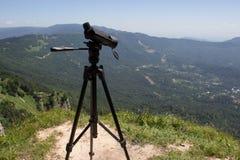 Ταξιδιώτης που φαίνεται η φύση από το υψηλό βουνό με την επισήμανση του πεδίου, τρίποδο διοπτρών στοκ φωτογραφίες με δικαίωμα ελεύθερης χρήσης