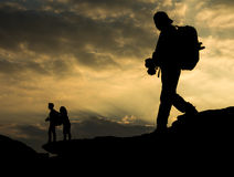 Ταξιδιώτης σκιαγραφιών με τη κάμερα και το ζεύγος στο βράχο στο s Στοκ Εικόνες