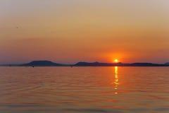 Ταπετσαρία ηλιοβασιλέματος της λίμνης Balaton με τα βουνά Badacsony Στοκ Εικόνα