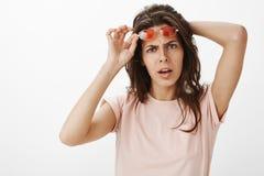 Ταραγμένη και ενοχλημένη νέα ελκυστική γυναίκα που βγάζει τα κόκκινα γυαλιά ηλίου ως συνοφρύωμα και εξέταση εξετασμένος τη κάμερα στοκ εικόνες
