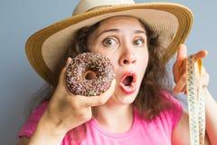 Ταραγμένη νέα γυναίκα που κρατά doughnut και μια μετρώντας ταινία Έννοια των γλυκών, του ανθυγειινών άχρηστου φαγητού και της παχ Στοκ εικόνα με δικαίωμα ελεύθερης χρήσης