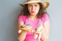 Ταραγμένη νέα γυναίκα που κρατά doughnut και μια μετρώντας ταινία Έννοια των γλυκών, του ανθυγειινών άχρηστου φαγητού και της παχ Στοκ Εικόνες