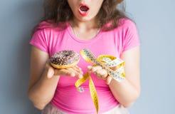 Ταραγμένη νέα γυναίκα που κρατά doughnut και μια μετρώντας ταινία Έννοια των γλυκών, του ανθυγειινών άχρηστου φαγητού και της παχ Στοκ Φωτογραφία