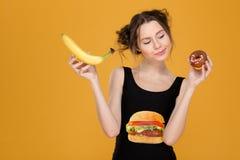 Ταραγμένη στοχαστική νέα γυναίκα που επιλέγει μεταξύ των υγιών και ανθυγειινών τροφίμων στοκ φωτογραφία
