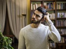 Ταραγμένος ή αμφισβητήσιμος νεαρός άνδρας που γρατσουνίζει το κεφάλι του και που ανατρέχει Στοκ φωτογραφία με δικαίωμα ελεύθερης χρήσης