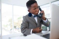 Ταραγμένος επιχειρηματίας που μιλά στο τηλέφωνο εξετάζοντας το lap-top Στοκ εικόνες με δικαίωμα ελεύθερης χρήσης