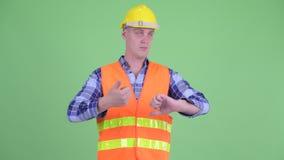 Ταραγμένος εργάτης οικοδομών νεαρών άνδρων που επιλέγει μεταξύ των αντίχειρων επάνω και των αντίχειρων κάτω απόθεμα βίντεο