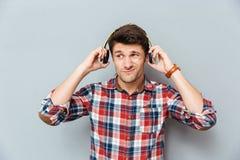 Ταραγμένος δυστυχισμένος νεαρός άνδρας στα ακουστικά που ακούει τη μουσική Στοκ Φωτογραφίες
