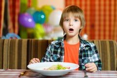 Ταραγμένο αγόρι με το μαχαίρι και δίκρανο μπροστά από τη σαλάτα Στοκ Φωτογραφία