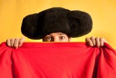 Ταυρομάχος φοβισμένος το μεγάλο καπέλο που κρύβεται με πίσω από το ακρωτήριο Στοκ Εικόνες