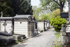 Ταφόπετρες στο νεκροταφείο στο σούρουπο, γοτθικοί σταυροί ύφους Στοκ Φωτογραφίες