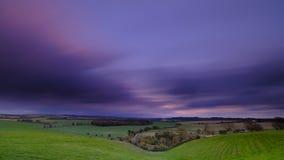 Ταχύτητα παραθυρόφυλλων Lonf του ζωηρόχρωμου ηλιοβασιλέματος φθινοπώρου πέρα από την κοιλάδα Hambledon που κοιτάζει προς την ευρε στοκ φωτογραφία