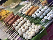Ταϊλανδική αγορά νύχτας με τα εθνικά τρόφιμα: τηγανισμένα ψάρια, σούσια, γλυκά ρυζιού, οβελίδια, σούσια, θαλασσινά στοκ εικόνες