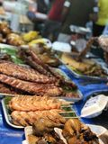 Ταϊλανδική αγορά νύχτας με τα εθνικά τρόφιμα: τηγανισμένα ψάρια, σούσια, γλυκά ρυζιού, οβελίδια, σούσια, θαλασσινά στοκ φωτογραφίες